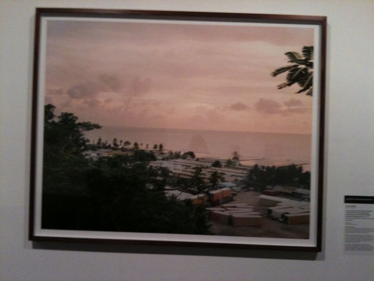 Kelvin Skewes (Born Australia 1988)  View towards former British Phosphlate Commission housing and regional Processing Centre portable buildings stored on Denig oval, Nauru. 2013 from the series 'What was taken and what was given.'  Ink-jet print