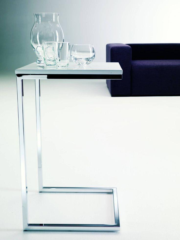 Kwadratowy stolik–pomocnik (bok 30 lub 40 cm) na C–kształtnej ramie. Blat malowany (biel lub czerń) albo drewniany (naturalny fornir dębowy wybarwiony na kolor mokka). Do tego rama lśniąca chromem.