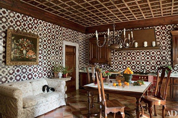 Outside Venice, Italy, a Studio Peregalli–designed kitchen has walls sheathed in majolica tile and a La Cornue range in a coordinating shade of burgundy. Antique dining chairs join the Carrara-marble-top table to form a casual eating space.