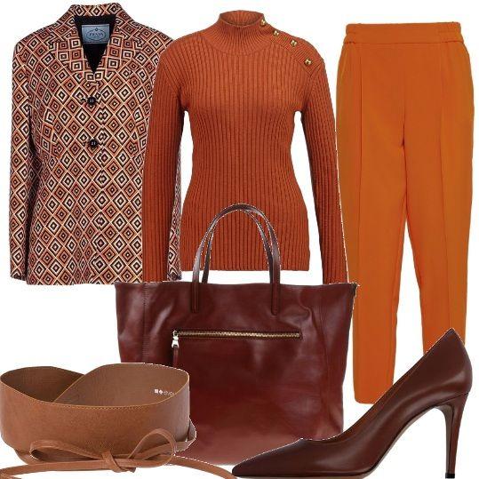 Pantalone dritto color arancio, dolcevita a costine color ruggine con bottoncini color oro decorativi sulla spalla, giacca a due bottoni in fantasia geometrica , cintura alta da legare con fiocco, borsa grande con tasche e manici color testa di moro, décolleté con tacco alto.