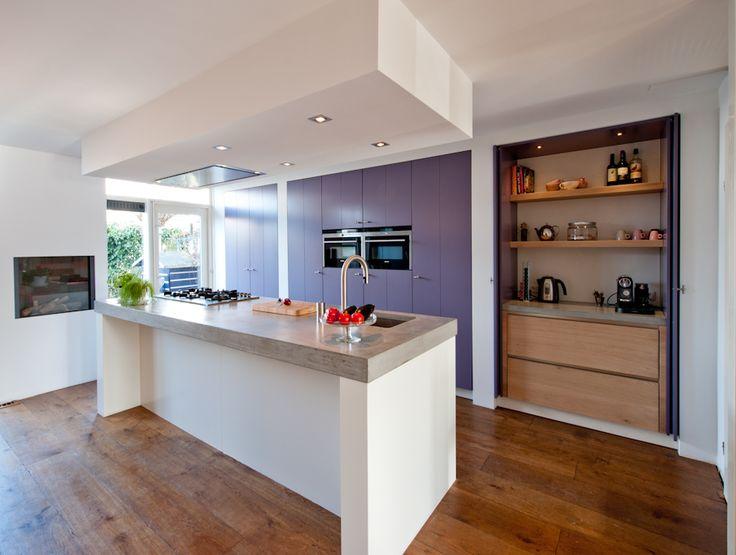 De oude keuken die langs de wand was opgesteld heeft plaatsgemaakt voor een modern keukeneiland waarbij de ruimte opnieuw werd ingedeeld en optimaal werd benut.
