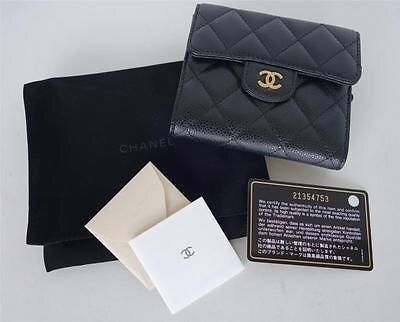 "This black quilted caviar leather compact wallet has a gold ""CC"" logo on the front flap, and inside has six credit card slots, two open pockets behind the credit card slots, and a larger pocket for bills. The back of the wallet has a zippered coin compartment. Interior is made of brown leather. Comes with a Chanel pouch, authenticity card, and booklet. Hologram sticker marked with serial number: 21354753, which matches the authenticity card. Approximate Measurements: 4.66 inches across..."