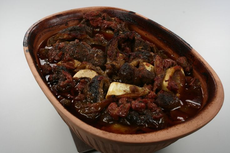 Gnid skiverne af kalveskanken med salt og peber og læg dem i stegesoen. Pres hvidløgssaft over kødstykkerne. Tilsæt tomatpure, flåede tomater, bouillon og rosmarin og basilikum. <BR> <BR> Steg