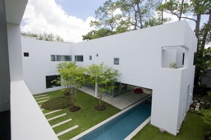 ein minimalistischer Garten im Inneren Hof voller Zierbäume und ein Kreis aus Gras
