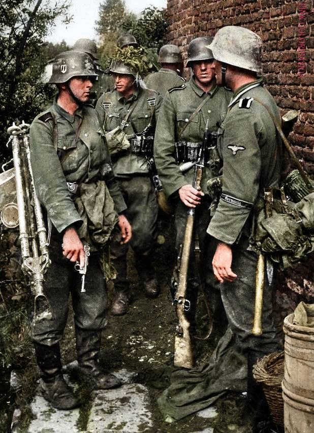 """SS soldiers wearing a Germania cuff title. The Regiment Germania left the """"Das Reich"""" in 1940 and became part of the 5th SS-Div. Deutschland, Germania and Der Führer, were organized into the SS-Verfügungs-Division with Paul Hausser as commander. In December 1940 the Germania Regiment was transferred from the Das Reich Division and used to form the cadre of a new division composed of 'Germanic' volunteers, mostly Danes, Norwegians, Dutch, and Belgian Wallons. Inicially named Germania, the…"""