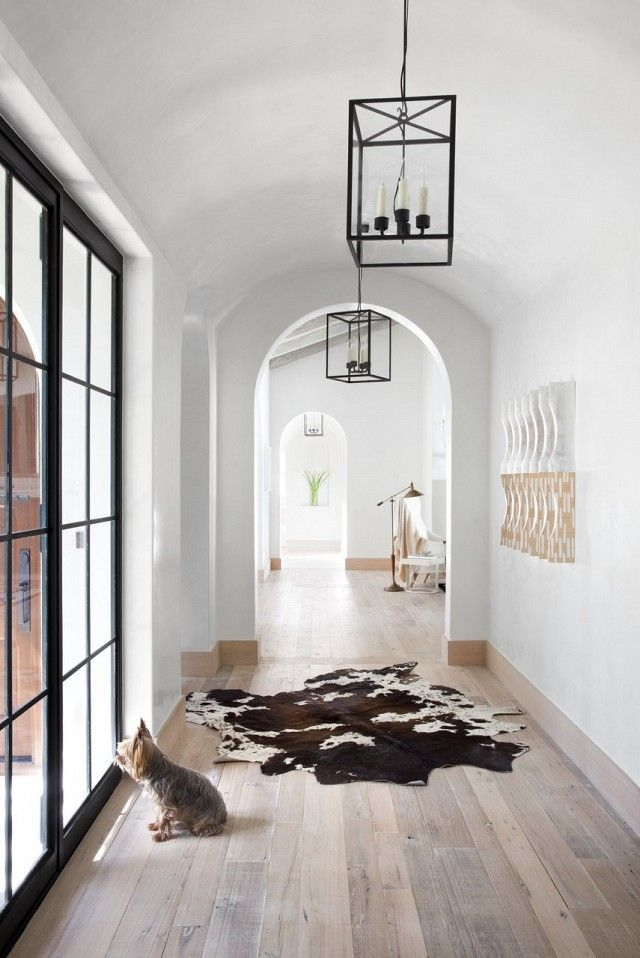 Hall with large windows, fur rug, and rustic pendant lamps. | @andwhatelse