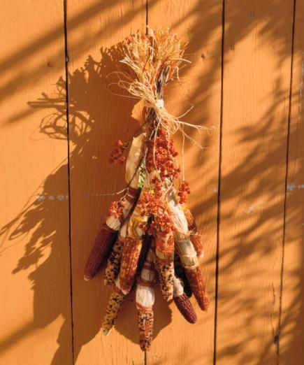 Welcome the season into your home with door decorations using ornamental corn, gourds, pumpkins and other autumn materials.
