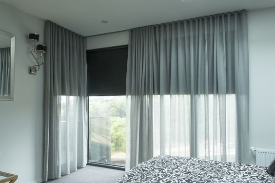 Roller blinds in dark gray, with sheer curtains