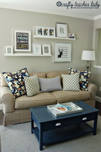 Cozy living room...like the pictures above the couch! would work well for scrolls, get rid of the one big picture...