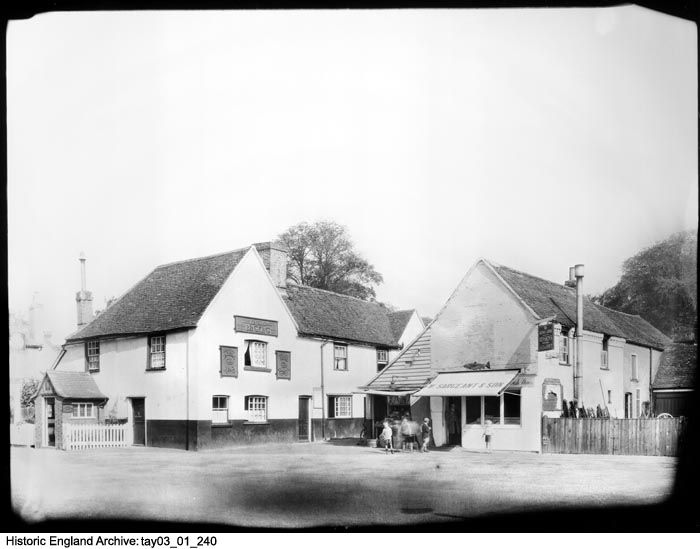 TAY03/01/240 A view looking towards W Sargeant and Son's fishmongers and The King's Arms in Harefield, Uxbridge in England.  This print is one of twenty showing public houses which, at the time of accession, were unidentified and so were separated from the rest of the collection. The King's Arms was tied to Benskins Brewery who held a number of public houses in and around Hertfordshire, Essex, Buckinghamshire and Berkshire.  Date1925 - 1935