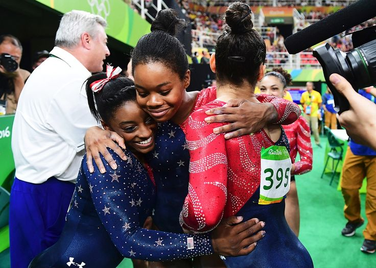 US gymnast Simone Biles, US gymnast Gabrielle Douglas and US gymnast Alexandra Raisman embrace during the qualifying for the women's Artistic Gymnastics at the Olympic Arena during the Rio 2016 Olympic Games in Rio de Janeiro on August 7, 2016.