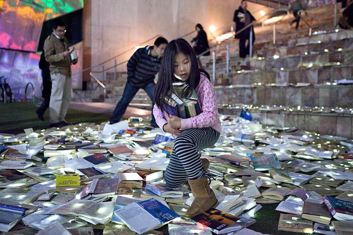 """Over 10,000 books thrown out by public libraries were recently given new life in a beautiful new lighting installation by Inhabitat favorites Luzinterruptus. Called """"Literature Versus Traffic"""", the installation spilled out into the streets of Melbourne during the Light in Winter festival, fusing discarded books with glowing LED lights. The river of glowing books invited passersby to leaf through the volumes that had been forsaken for the dump and take them home."""