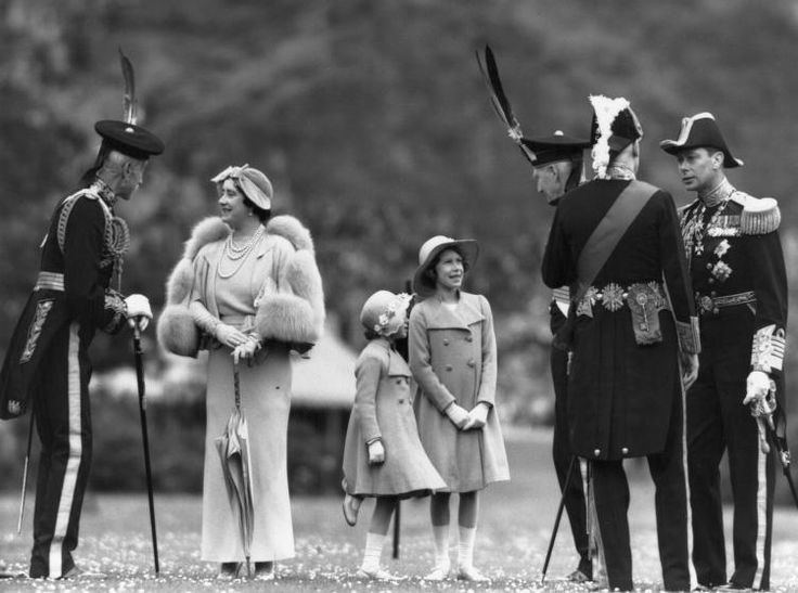 Queen Elizabeth talking to Lord Elphinstone during an inspection of the Royal Company of Archers at the Palace of Holyroodhouse, Edinburgh. Her husband King George VI is on the right; Princesses Elizabeth and Margaret Rose are in the center. July 1937.