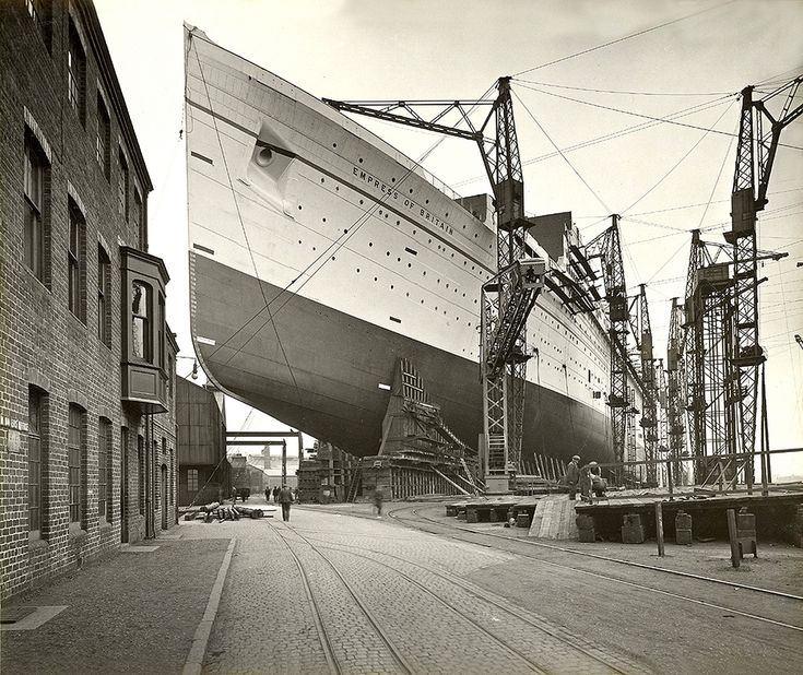 "1931:RMS Empress of Britain under construction. ""The RMS Empress of Britain was an ocean liner built between 1928 and 1931 by John Brown shipyard in Scotland and owned by Canadian Pacific Steamship Company, providing trans-Atlantic passenger service between Canada and Europe from 1931 until 1939.  ""She was torpedoed on 28 October 1940 by U-32 and sank. She was the largest liner lost during the Second World War and the largest ship sunk by a U-boat."""