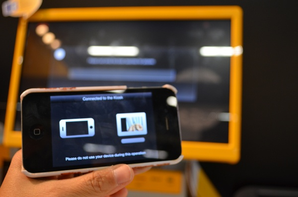 Mobile phone and Kiosk Screen in background