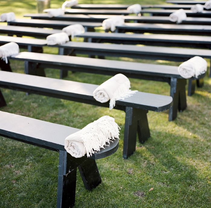 Blankets on benches for an outdoor wedding