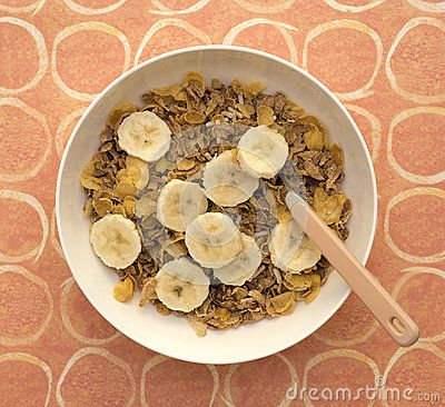 A white bowl of multi grain breakfast cereal and spoon topped with sliced banana on a patterned placemat.