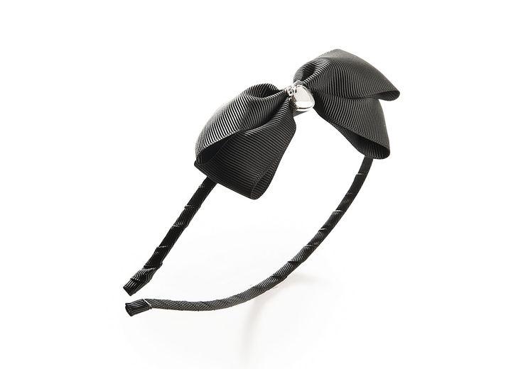 Musta rusettipanta, jossa hopeanvärinen sydän rusetin koristeena.