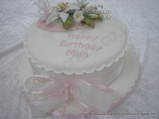 Elegant round traditional style birthday cake. Covered in simple white icing, tied together with a pink chiffon ribbon and bow, and finished with a sugar flower spray and colour matching birthday message