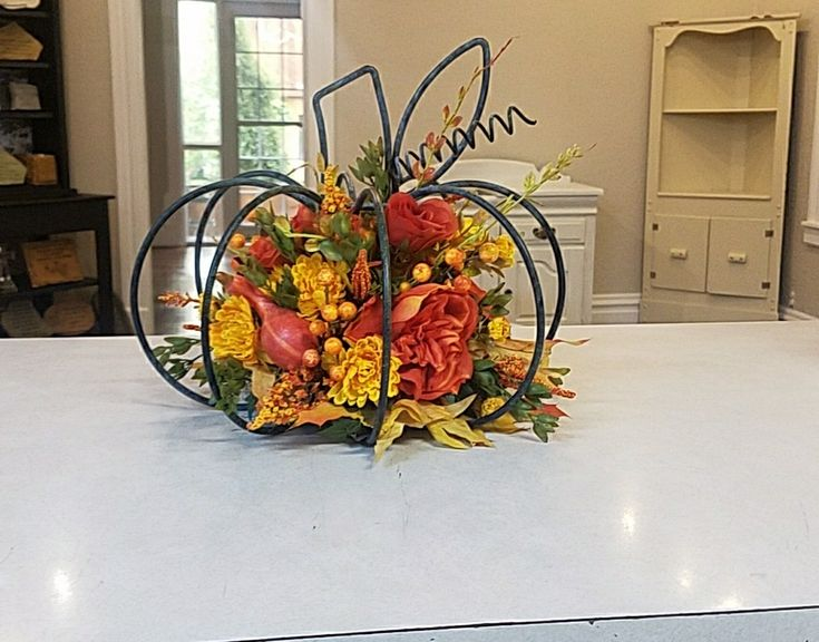 Fall wrought iron pumpkin with artificial floral arrangement in the middle.
