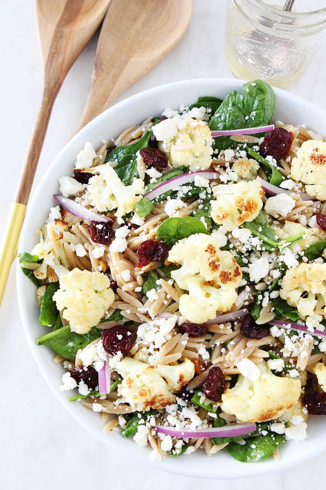 Roasted Cauliflower, Feta, and Orzo Salad Recipe on twopeasandtheirpod.com Spinach salad with roasted cauliflower, orzo, feta cheese, dried cherries, red onion, and a simple honey lemon dressing. This salad is great for lunch or dinner.
