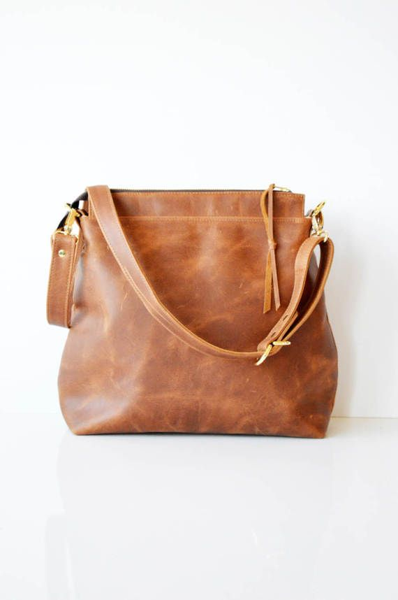 Leather hobo bag in soft toffee cowhide leather with zipper closure and long adjustable leather crossbody strap *** This bag is hand made to order - please allow up to 3 weeks production time *** --DESCRIPTION-- > A hobo style leather bag that can be worn on the shoulder or across the body > Made from beautiful toffee colored strong and supple cowhide with an antiqued effect, this leather will acquire a beautiful patina as it is used. > Lined in 100% oatmeal linen, with a zipp...