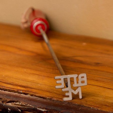 """Bite Me BBQ Branding Iron by Texas Irons. $24.95. FREE SHIPPING! Ships same day if ordered by 1PM EST. Measures 14"""" long; Brand head measures ~2"""" x 1"""". Make your mark with this BBQ Branding Iron. Perfect for steaks, burgers, chicken or just about anything you can grill. Durable stainless steel shaft with wood handle can endure intense grilling heat. A Texas Irons original! This custom-made BBQ brand features the playful phrase """"BITE ME"""" - perfect for leaving your mark on just a..."""