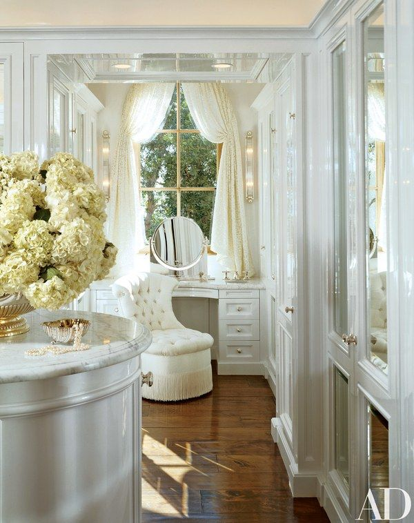 """The wife's dressing area in the master suite. High-gloss lacquered walls provide """"a spacious, cool, glamorous effect,"""" Wright notes. The tufted-button slipper chair lends an Art Déco-style flair. A George III silver punch bowl is on a marble-topped island. Ron Seff custom vanity mirror."""