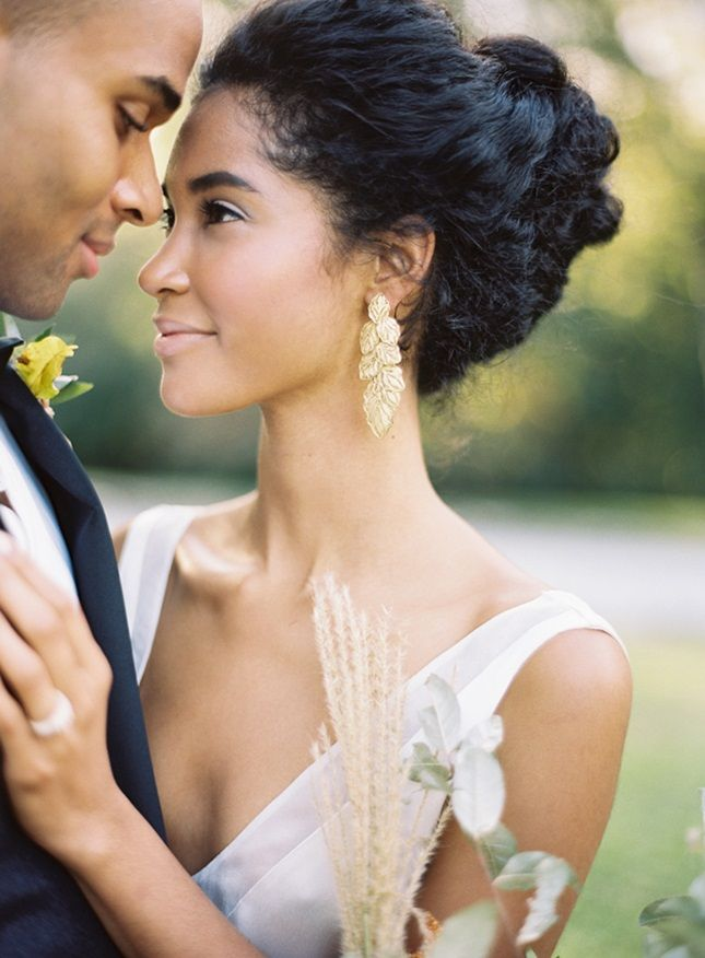 Regal Tie-Back. Work the aisle like a goddess by pulling thick hair back into a regal knot, then dialing up the drama with a pair of shimmering gold earrings.