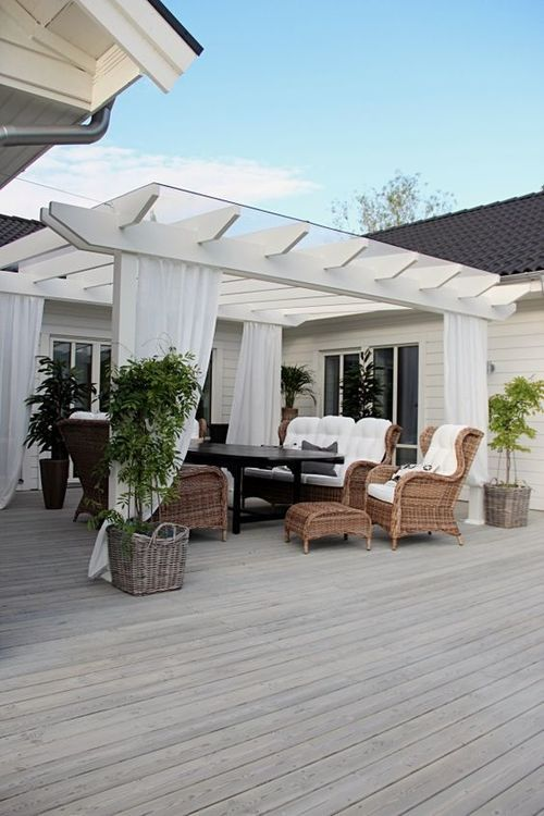 charming white deck pergola with wicker furniture, quaint & chic