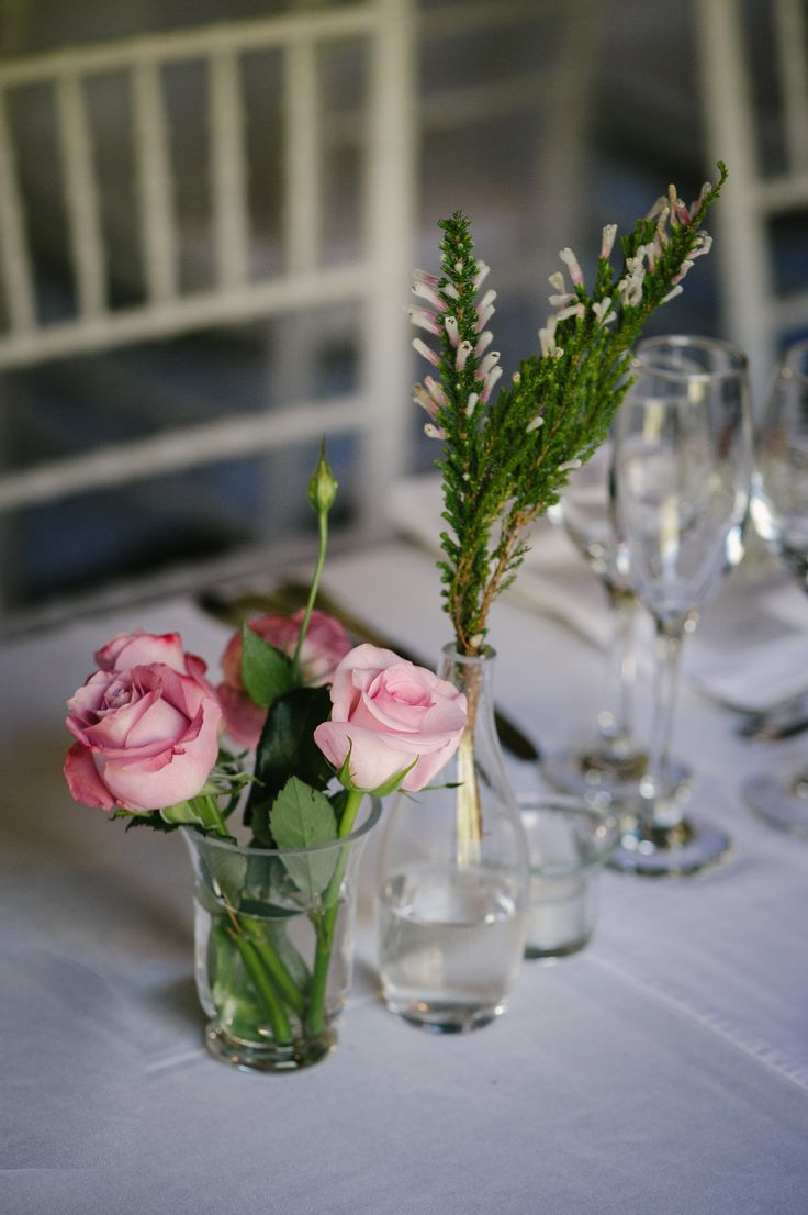 Don't be afraid to use single sprigs of fynbos in clear glass vases for your tables. Complement with roses in a soft tone for a rustic but elegant look.