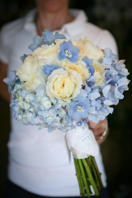 blue and white wedding bouquet designed with blue hydrangea light blue delphinium blossoms and fragrant white garden roses