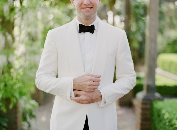 Groom wearing white dinner jacket with black bowtie and trousers