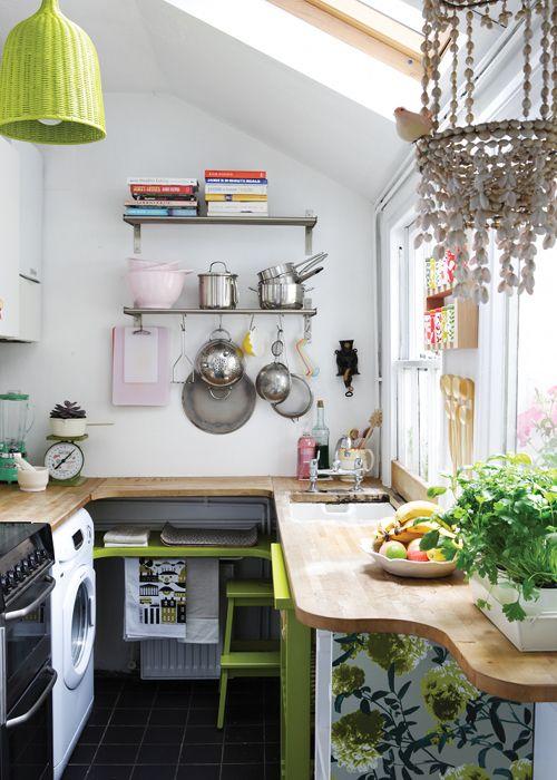 Cette petite cuisine au charme bohême - qui accueille aussi l'espace buanderie avec le lave-linge - mise sur des couleurs gaies (rose layette et vert pomme) pour apporter de la joie dans un espace étriqué.