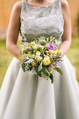 Grey wedding dress with lace and grey-violet rustical bouquet.