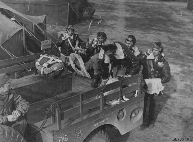 Brazilians who fly Republic P-47 Thunderbolts in the First Brazilian Fighter Squadron in Italy climb into a weapons carrier to ride down to the line