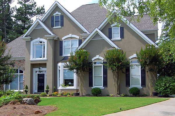 Front View Of Stucco Home And Trim Black Shutters