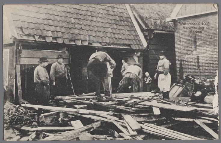Schade aan de huizen door de overstroming. Opruimen van rommel en herstellen van de schade. Kerkbuurt - Breihoek. Tweede man van rechts is Jan Dolfijn. De man met witte broek is K. Visser Czn. van Keet. Watersnood 1916 #NoordHolland #Marken