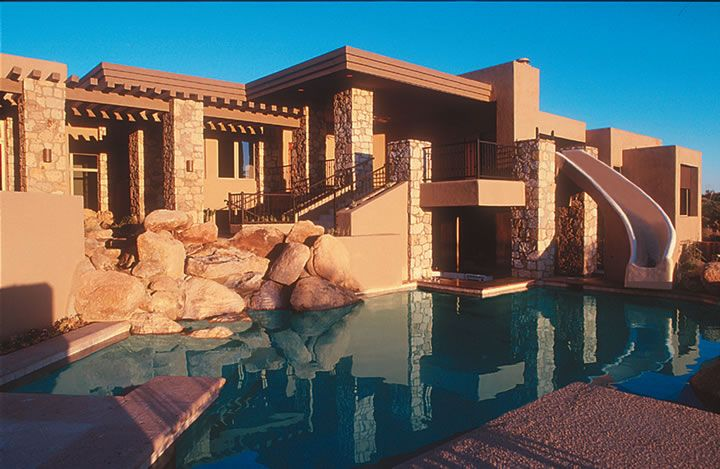 Traditional Southwest style home features a built in pool & water slide, with a swim-up bar area next to a barbecue and dining patio