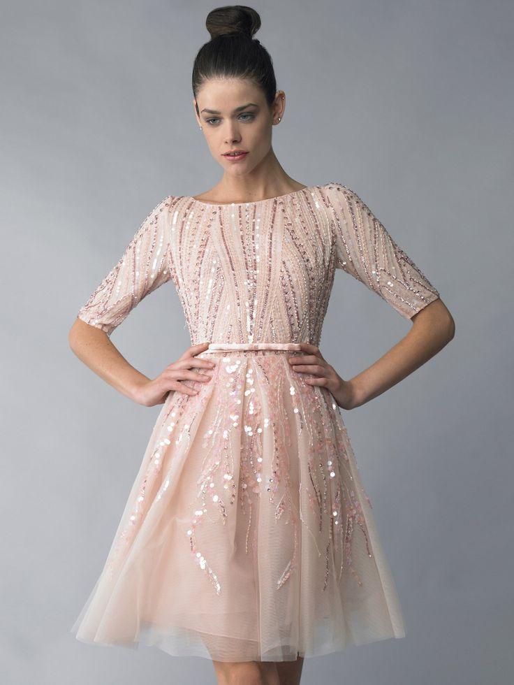 Короткое вечернее платье с пышной юбкой А-силуэта смотрится очень торжественно и ярко, несмотря на свой нежный пастельный оттенок ткани. Вырез лодочка и рукав длиной до локтя уравновешивают легкомысленную воздушную юбку, делая образ сдержаннее.  В качестве отделки использованы розовые пайетки в тон ткани и бисер, которые плотным геометрическим узором покрывают верх платья и свободнее располагаются на ткани низа.