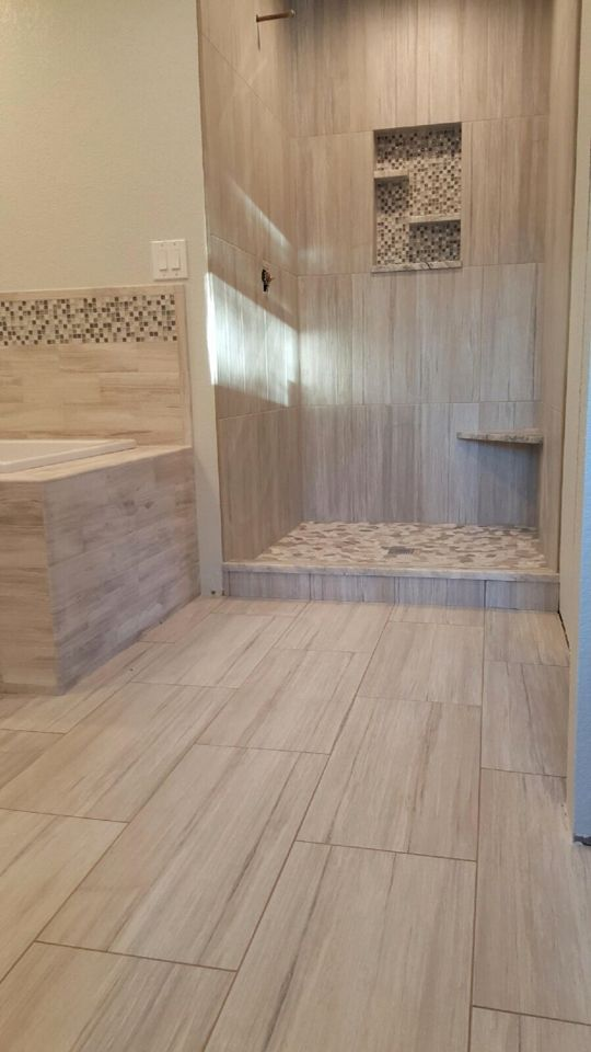 "Contemporary shower design. 12x24 wall tile set vertical ""stacked"". Complete with a floating corner bench and pebble pan. Pan tile was set individually and not from a mat. Work done by Glueks Custom."