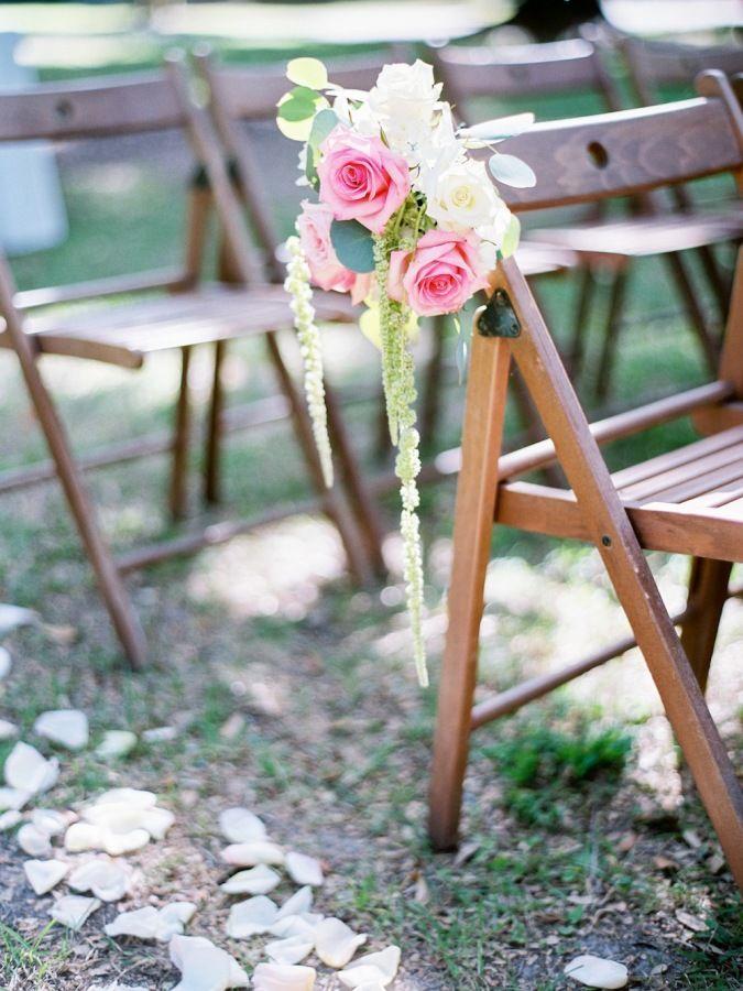 Pretty floral adorned ceremony chair: http://www.stylemepretty.com/south-carolina-weddings/pawleys-island-south-carolina/2015/09/01/traditional-elegant-south-carolina-wedding/ | Photography: Paula Player - http://paulaplayer.com/