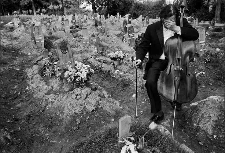 Cellist Vedran Smailovic breaks down in tears after playing a requiem to a dead friend at Hero's Cemetery, where Bosnian fighters were buried during the siege of Sarajevo in 1992.