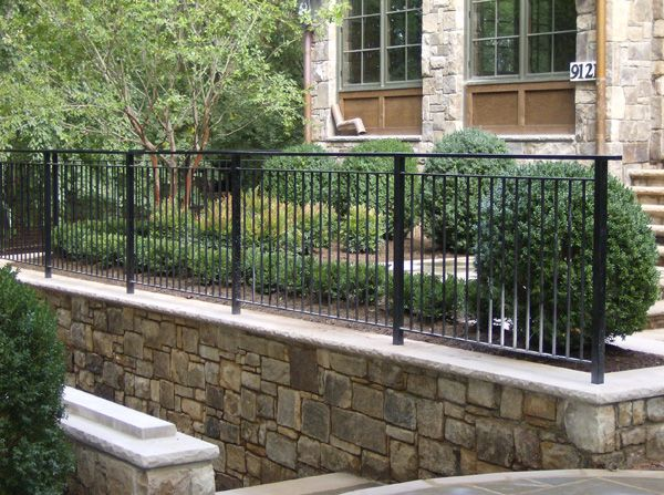 Courtyard with retainer wall and iron fencing