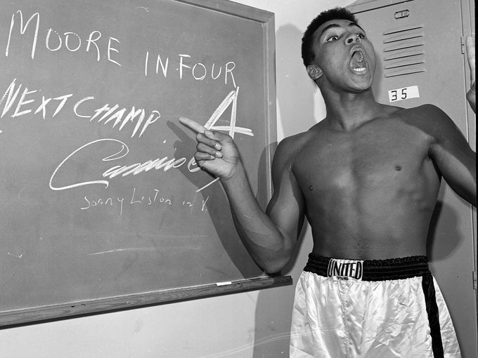Young heavyweight boxer Cassius Clay points to a sign he wrote on a chalk board in his dressing room before his fight against Archie Moore in Los Angeles, in this Nov. 15, 1962, file photo predicting he'd knock Moore out in the fourth round, which he went on to do.