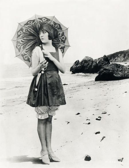 1920s movie star Lila Lee posing on a beach with a parasol and fabulous swimwear.