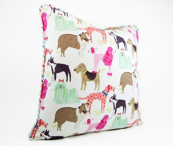 This adorable decorative dog pillow cover features a variety of breeds including pink poodles, collies, malteses, and boxers and would look