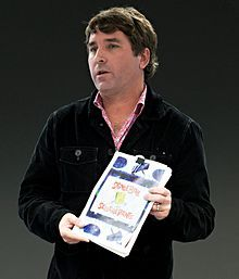 A photograph of a middle-aged man standing and holding a book