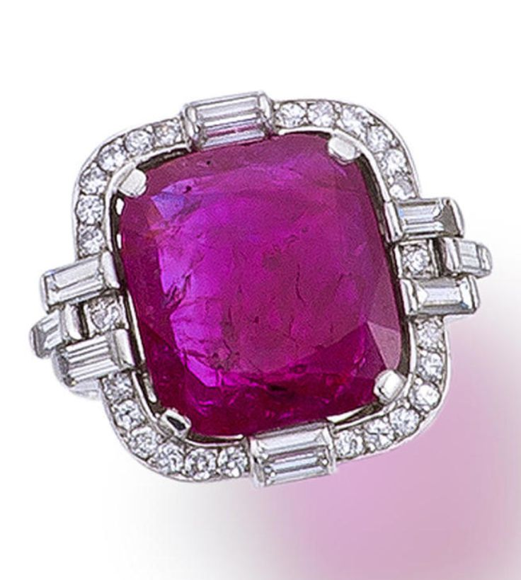 A ruby and diamond ring, French  centering a cushion-shaped ruby within a surround of round brilliant-cut diamonds and further detailed with baguette-cut diamonds; with maker's mark for Charles Hall. Art Deco or Art Deco style.
