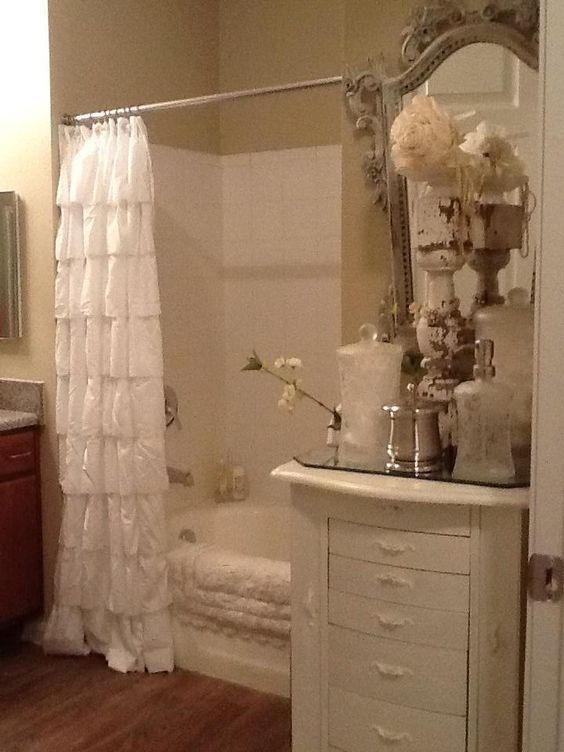 """brindledog: """"A ruffled shower curtain and small cabinet w/accessories give this bath a French flair. """""""